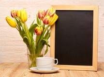 Leeres Brett, Blumen und Tasse Kaffee Stockfotografie