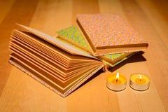 Leeres Buch am Licht der Kerzen stockfotografie