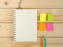 Leeres Buch und bunter Bleistift und Notizblock auf dem hölzernen Schreibtisch Lizenzfreies Stockfoto