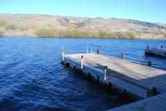 Leeres Dock auf einem tiefen blauen See Stockbilder
