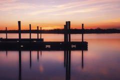Leeres Dock auf Wasser unter einem rosa und orange Sonnenuntergang Stockfotos