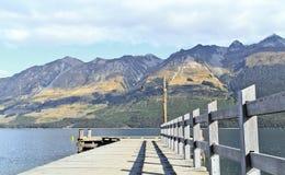 Leeres Dock im ruhigen See Stockfotos