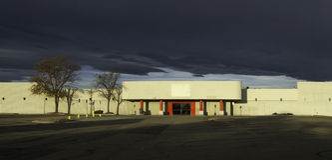 Leeres Einzelhandelsgeschäft mit ominösen Wolken oben Lizenzfreies Stockfoto