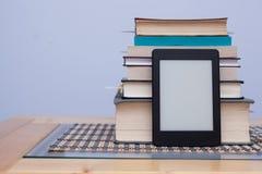 Leeres eReader vor einem Turm von Büchern mit Bookmarks Stockfotos