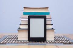 Leeres eReader vor einem Turm von Büchern mit Bookmarks Stockfotografie