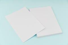 Leeres Fliegerplakat, Broschürenmodell, A4, Uns-Buchstabe, auf blauem backg Lizenzfreie Stockbilder