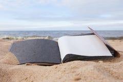 Leeres Fotoalbum auf Sand nahe dem Meer Stockbild