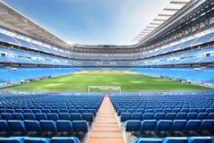 Leeres Fußballstadion mit Sitzen, gerollten Toren und Rasen Lizenzfreie Stockfotos