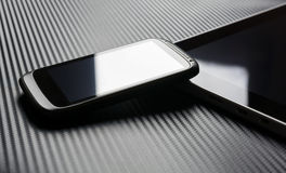 Leeres Geschäft Smartphone mit der Reflexion, die auf Tablet mit Kohlenstoff-Hintergrund sich lehnt Stockbild