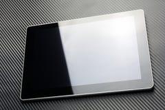 Leeres Geschäfts-Tablet mit der Reflexion, die auf Kohlenstoff-Hintergrund liegt Stockbilder