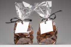 Leeres Geschenk etikettiert mit Band auf zwei Schokoladentrüffeltaschen Stockfoto