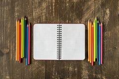 Leeres gewundenes Notizbuch und farbige Bleistifte Stockfotografie