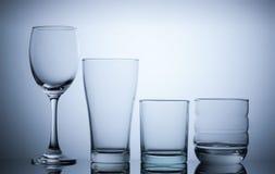 leeres Glas der Gruppe auf Blaulichthintergrund Stockfoto