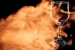 Leeres Glas Rotwein im Feuer flammt stockfoto