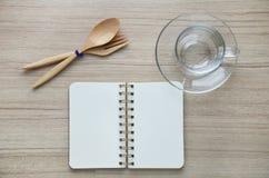 Leeres Glas und Notizbuch auf der hölzernen Tischplatteansicht Lizenzfreie Stockfotos