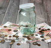 Leeres Glasgefäß und russisches Geld auf dem Bretterboden Stockbilder