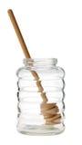 Leeres Glashonigglas mit dem Schöpflöffel lokalisiert Stockfotos