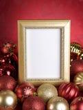 Leeres Goldfeld mit Weihnachtsverzierungen auf einem roten Hintergrund Stockbilder