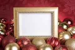 Leeres Goldfeld mit Weihnachtsverzierungen auf einem roten Hintergrund Stockbild