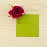 Leeres Grünbuch und rosafarbene Blume auf hölzernem Hintergrund Stockfoto