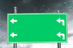 Leeres grünes Schild auf dem Regnen und Tau Stockfotografie