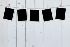 Leeres Hängen des Rahmens mit fünf Fotos am Hintergrund des hölzernen Brettes stockfoto