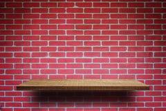 Leeres hölzernes Regal auf Backsteinmauer lizenzfreies stockbild