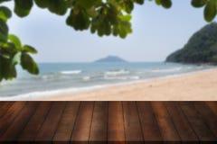 Leeres hölzernes Regal mit Blattrahmen auf undeutlichem Strand und Meer Holz Lizenzfreies Stockfoto