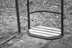 Leeres hölzernes Schwingen für Baby oder älteres Kind am eingezäunten lokalen Spielplatz Lizenzfreies Stockbild