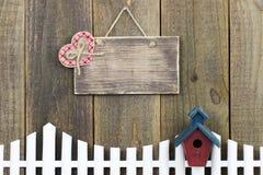 Leeres hölzernes Zeichen mit dem Plaidherzen, das über weißem Palisadenzaun mit Vogelhaus hängt Stockfotos