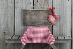 Leeres hölzernes Zeichen mit rotem Herzen über Picknicktisch Lizenzfreie Stockbilder