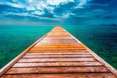 Leeres hölzernes Dock über tropischem blauem Wasser Stockbild