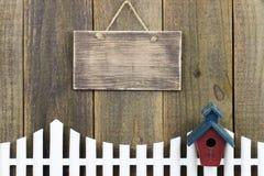 Leeres hölzernes Zeichen, das über weißem Palisadenzaun mit Vogelhaus hängt Stockbilder