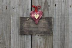 Leeres Holzschild mit den roten Gingham- und Goldherzen, die am hölzernen Hintergrund hängen Stockfoto