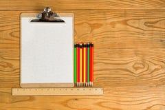 Leeres Klemmbrett mit den Papier- und bunten Bleistiften auf dem Desktop Lizenzfreies Stockfoto