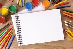 Leeres Kunstbuch oder Skizzenauflage mit Kunstausrüstung, Farben auf Schulbank, Kopienraum Lizenzfreies Stockbild
