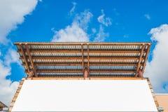 Leeres LeerraumAnschlagbrett mit Holz- und Zinkdach mit blauem Himmel Bereiten Sie für Produktanzeigen-Montage vor Stockfoto