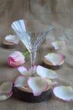 Leeres Martini-Glas und rosafarbene Blumenblätter Stockfotografie
