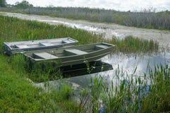leeres Metallboot auf einem Sumpf an einem bewölkten Tag lizenzfreie stockfotografie