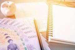 Leeres Notizbuch, Bleistift, Sparkontosparbuch, Augengläser, thailändisches Geld und Sparschwein auf grauem Hintergrund Stockfotos