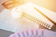 Leeres Notizbuch, Bleistift, Sparkontosparbuch, Augengläser, thailändisches Geld und Sparschwein auf grauem Hintergrund Lizenzfreies Stockfoto