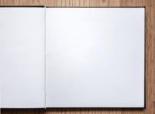 Leeres Notizbuch geöffnet auf hölzernem Hintergrund Stockfotografie