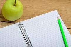 Leeres Notizbuch mit Apfelfrucht Lizenzfreie Stockfotos