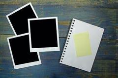 Leeres Notizbuch mit Aufkleber- und Fotorahmen auf hölzernem Hintergrund Stockbilder