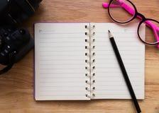 Leeres Notizbuch mit einem Bleistift und Brillen Stockbilder
