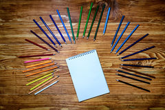 Leeres Notizbuch mit Farbe zeichnet auf dem Holztisch an Lizenzfreie Stockfotos
