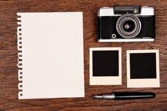 Leeres Notizbuch mit Stift, Fotorahmen und Kamera Stockfotografie