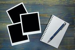 Leeres Notizbuch mit Stift- und Fotorahmen auf hölzernem Hintergrund Lizenzfreies Stockbild