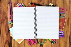 Leeres Notizbuch mit zugrunde liegendem Rahmen des Schulbedarfs über Holz lizenzfreie stockbilder