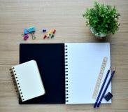 Leeres Notizbuch und Druckbolzen auf der hölzernen Tischplatteansicht Lizenzfreie Stockfotografie